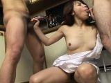 Asian housewife works her hands and lips on two cocks in the kitchen